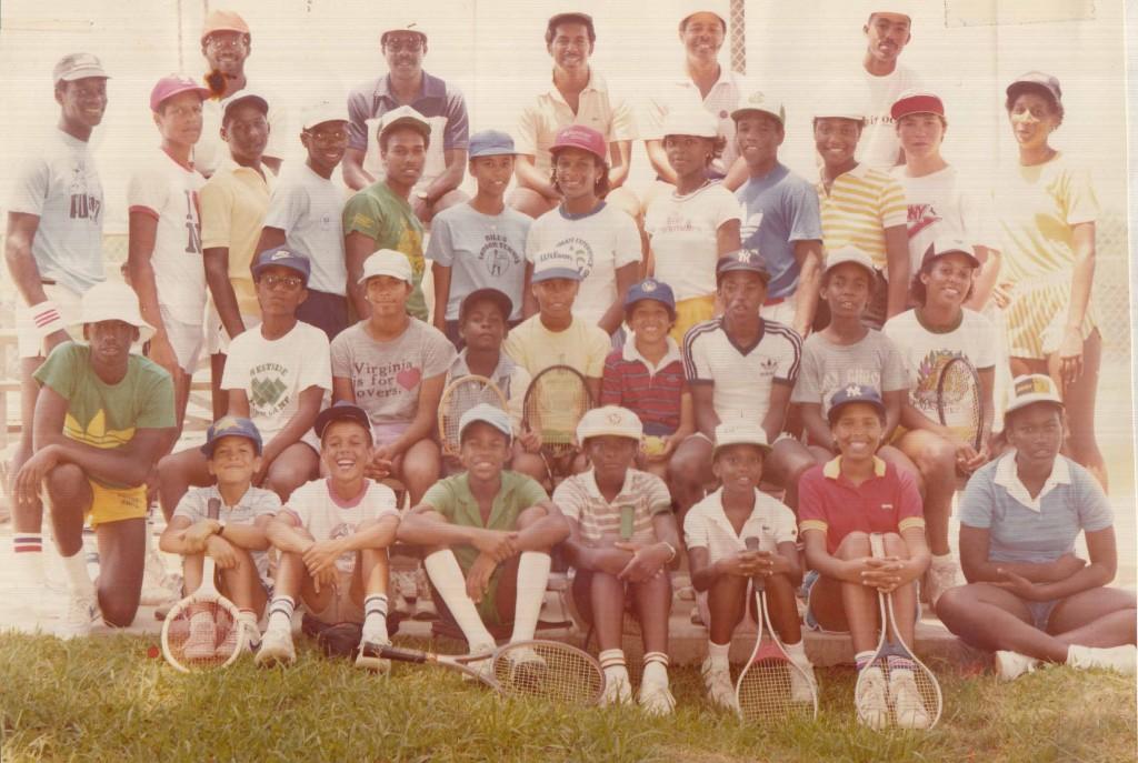 "Members of the MacGregor Park Junior Tennis Program. Front row, seated, left to right: Jason Moran, David Marshall, Akida Mashaka, Jennifer Alexander, Priscilla Alexander, Tracey Holmes, and Fialka Milburn. Second row, kneeling, left to right: Terry (last name unknown), Felix (last name unknown), Faye (last name unknown), Atari (last name unknown), Shelly Mack, Michael Holmes, Thomas ""Goose"" Middleton, Morris (last name unknown), and Tina Haskins. Third row, standing, left to right: Thomas (last name unknown), Jeffrey Addison, Ramondo Mosley, Rayn Ross, Michael Curry, Melissa Kemp, Zina Garrison, Lisa Lang, name unknown, Mattie Middleton, unknown name, and Kathy Foxworth. Top row, standing, left to right: Sydney (last name unknown), Edgar Arnold, John Wilkerson, Willis (coach from Washington D. C.), and Rodney Harman. Photo courtesy of Michon Benson."